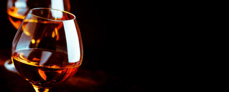 Grape brandy in shot glass, dark brown background. Panoramic banner with copy space Stock Photo