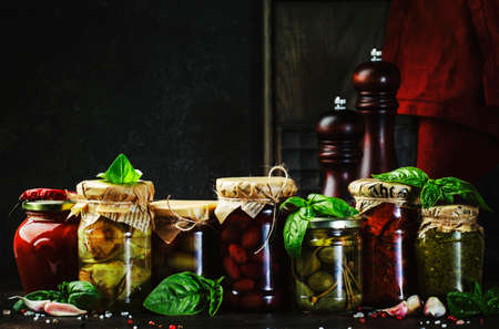 Canned food concept. Fermented, pickled, marinated preserved vegetarian italian snacks and sauces. Organic sun-dried tomatoes, artichokes, capers, olives, marinara sauces, pesto in jars with spice and herbs on black kitchen table