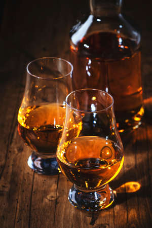 Scotch Whiskey without ice in glasses and bottle, rustic wood background, copy space
