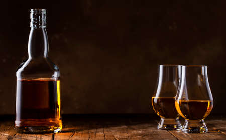 Scotch Whiskey without ice in glasses and bottle, rustic wood background, copy space banner
