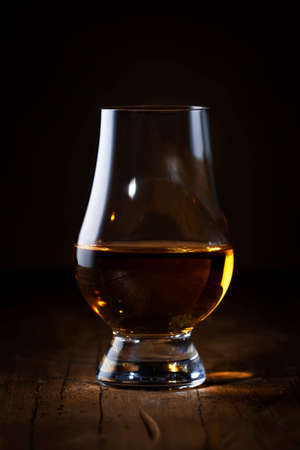 Scotch Whiskey without ice in glass, rustic wood background, copy space