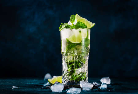 Mojito cocktail or mocktail with lime, mint, and ice in glass on blue background. Summer cold alcoholic non-alcoholic drink, beverage and cocktail. Copy space Reklamní fotografie