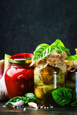 Canned food concept. Fermented, pickled, marinated preserved vegetarian italian snacks and sauces. Organic sun-dried tomatoes, artichokes, capers, olives, marinara sauces, pesto in jars with spice and herbs on black kitchen table Reklamní fotografie