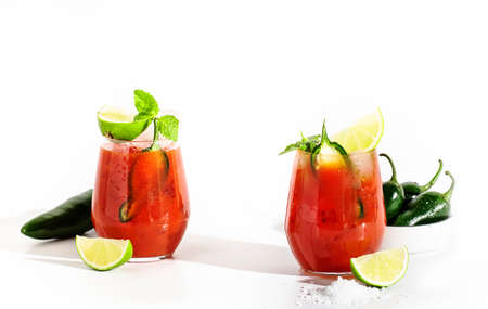 Spicy alcoholic cocktail with vodka, tomato juice, jalapeno pepper, lime and salt, white background, hard light, copy space