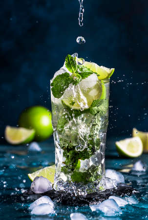 Mojito with splash and drops. Cocktail or mocktail with lime, mint, and ice in glass on blue background. Summer cold alcoholic non-alcoholic drink, beverage and cocktail. Copy space