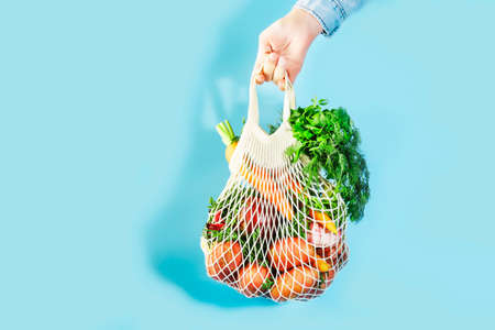 Mesh bag with vegetables and herbs in female hand. Woman hold string net shopping bag on blue background. Modern reusable shopping, eco friendly lifestyle, zero waste concept. Banner