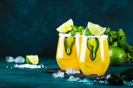 Spicy margarita cocktail with tequila, mango juice, jalapeno pepper, lime and salt, blue background, copy space