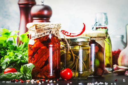Canned food concept. Fermented, pickled, marinated preserved vegetarian italian snacks and sauces. Organic sun-dried tomatoes, artichokes, capers, olives, marinara sauces, pesto in jars with spice and herbs on gray kitchen table Reklamní fotografie