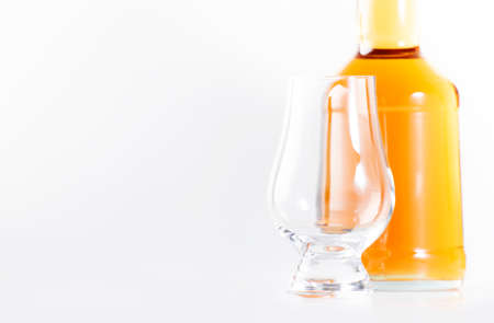Scotch Whiskey without ice empty glasses and bottle, white background, copy space