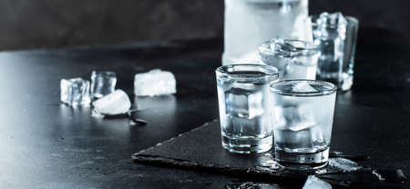 Vodka in shot glasses on black stone background, iced strong drink in misted glass