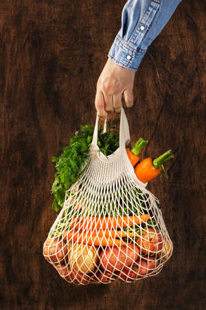 Mesh bag with vegetables and herbs in female hand. Woman hold string net shopping bag on wooden background. Modern reusable shopping, eco friendly lifestyle, zero waste concept