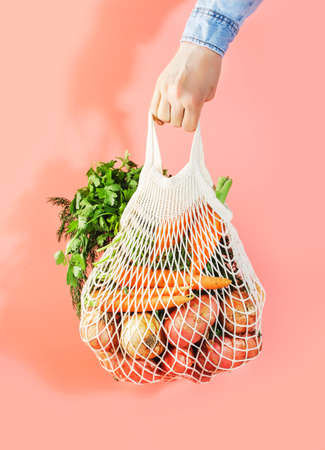 Mesh bag with vegetables and herbs in female hand. Woman hold string net shopping bag on pink background. Modern reusable shopping, eco friendly lifestyle, zero waste concept. Reklamní fotografie