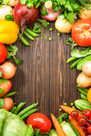 Assortment of fresh vegetables on wooden table frame background. Healthy organic food grocery concept. Copy space