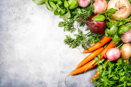 Assortment of fresh root vegetables and spicy herbs. Healthy food, summer cooking concept. Gray background with copy space. Top view