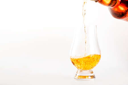Scotch Whiskey without ice in glass pouring out of the bottle, white background, copy space Reklamní fotografie