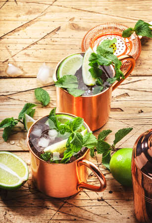 Moscow mule cocktail in copper mug with lime, ginger beer, vodka and mint. Wooden table, top view, copy space