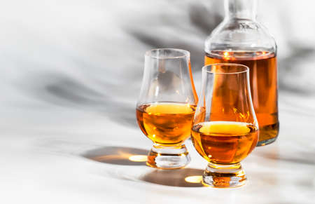 Scotch Whiskey without ice in glasses and bottle, white background with hard light, shadows and sun glare, copy space