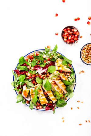 Fresh Salad with chicken breast, spinach, arugula, cedar nuts and pomegranate seeds. Healthy food and eating concept. Top view. White kitchen table