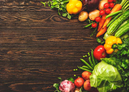 Assortment of fresh vegetables on wooden table background. Healthy organic food grocery concept. Copy space