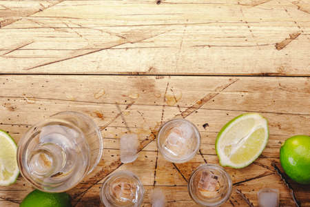 Vodka or tequila in shot glasses with lime on wooden background, iced strong drink in misted glass. Top view