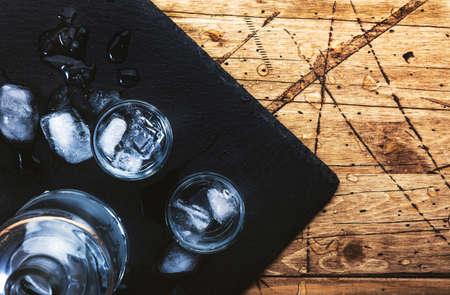 Vodka in shot glasses on wooden background, iced strong drink in misted glass. Top view