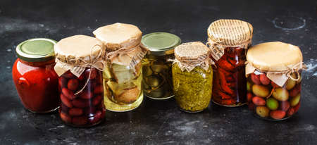 Canned food concept. Fermented, pickled, marinated preserved vegetarian italian snacks and sauces. Organic sun-dried tomatoes, artichokes, capers, olives, marinara sauces, pesto in jars with spice and herbs on gray kitchen table
