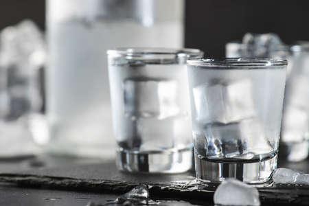 Vodka in shot glasses on black stone background, iced strong drink in misted glass Standard-Bild