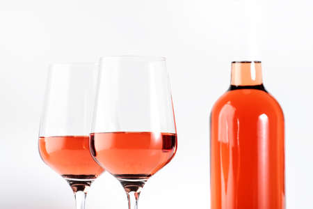 Rose wine glass with bottle on the white table. Banco de Imagens