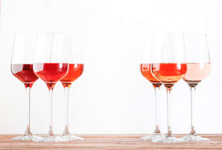 Rose wine glasses set on wine tasting. Tasting different varieties, colors and shades of pink wine concept. White background