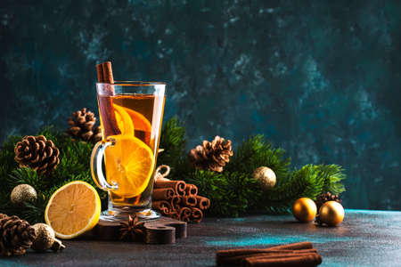 Christmas or New Year hot winter drink, spicy grog cocktail, punch or mulled wine with tea, lemon, rum, cinnamon, anise. Rustic style, festive table setting, copy space