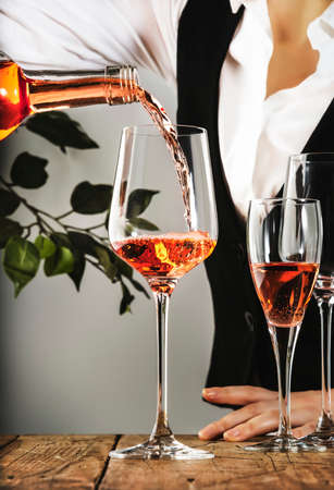 Sommelier pouring rose wine into glass at wine tasting in winery, bar or restaurant. Banco de Imagens