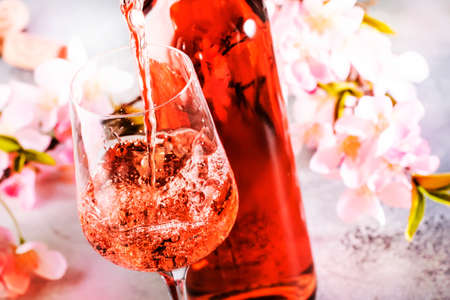 Rose wine pouring out of the bottle, gray bakcground, pink flowers. Rosado, rosato or blush wine tasting in wineshop, bar concept. Copy space Banco de Imagens