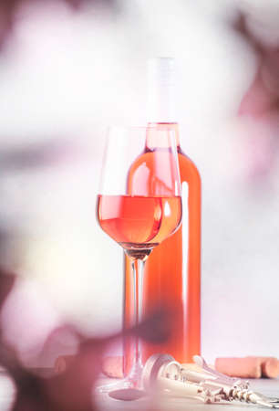 Rose wine glass with bottle on the gray table. Pink rosado, rosato or blush wine tasting in wineshop, bar concept. Copy space Banco de Imagens