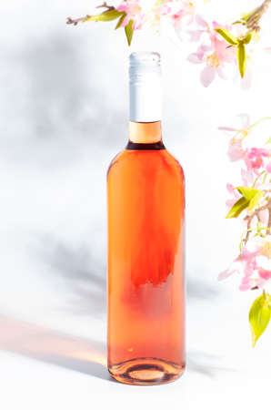 Rose wine bottle on the white table and pink flowers. Rosado, rosato or blush wine tasting in wineshop, bar concept. Copy space