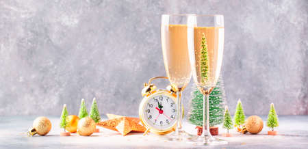 Two champagne glasses and christmas decoration over gray golden bokeh background. Happy New Year Celebration. Selective focus and small depth of field