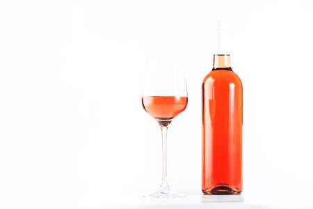 Rose wine glass with bottle on the white table. Rosado, rosato or blush wine tasting in wineshop, bar concept. Copy space Banco de Imagens