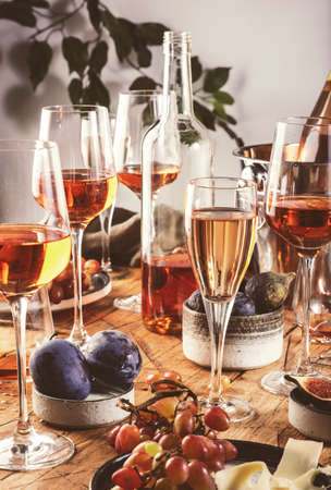 Rose wine glasses and bottles on table served for festive dinner party with different kinds of appetizers and fruits Banco de Imagens