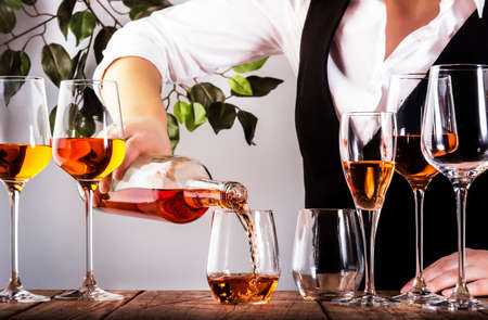 Sommelier pouring rose wine into glass at wine tasting in winery, bar or restaurant. White background