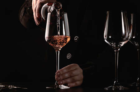 Sommelier pouring rose wine into glass at wine tasting in winery, bar or restaurant. Dark background Banco de Imagens