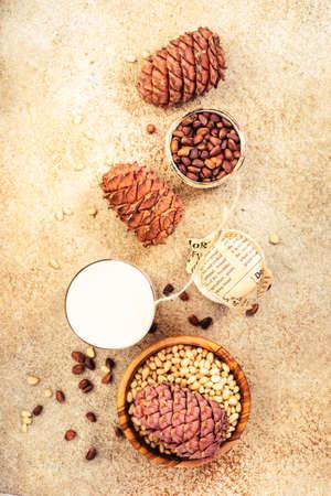 Cedar nut milk, beige table background. Non dairy alternative milk. Healthy vegetarian food and drink concept. Copy space, top view