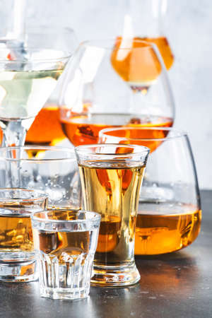 Strong alcoholic drinks in glasses in assortment: vodka, cognac, tequila, brandy and whiskey, grappa, liqueur, vermouth, tincture, rum. Gray bar counter with copy space