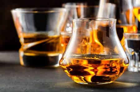 Hard strong alcoholic drinks and distillates in glasses in assortment: vodka, cognac, tequila, scotch, brandy and whiskey, grappa, liqueur, vermouth, tincture, rum. Brown background