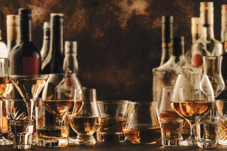 Hard strong alcoholic drinks and distillates in glasses and bottles in assortment: vodka, cognac, tequila, scotch, brandy and whiskey, grappa, liqueur, vermouth, tincture, rum. Brown background