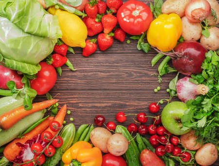 Healthy food. Assortment of fresh summer organic vegetables, fruits and berries on wooden table background
