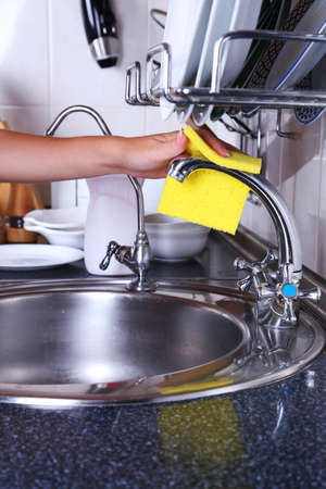 Cleaning the kitchen sink with sponge photo