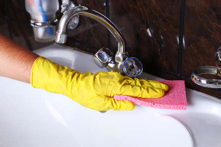 Male hand in gloves with sponge cleaning bathroom photo