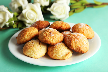 Coconut cookies on plate on green background photo