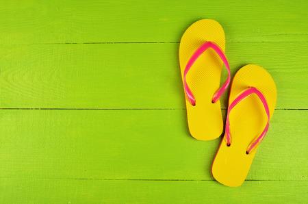 verano: Chancletas amarillo sobre fondo verde de madera