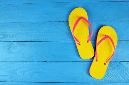 white sand: Flip Flops Yellow on blue wooden background