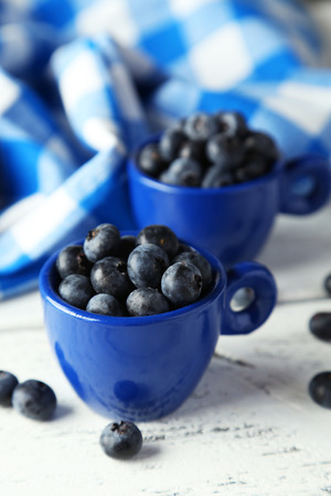 Blueberries in cup on white wooden background photo